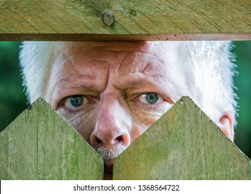 A curious man is watching over a wooden fence. Concept curiosity.
