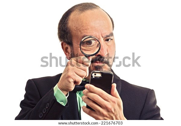 Curious. Mature business man looking through a magnifying glass on smart phone isolated  white  background. Human face expression. Investigator looking with magnifying glass. Security safety concept