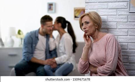 Curious mother-in-law secretly listening woman whispering secret on husband ear