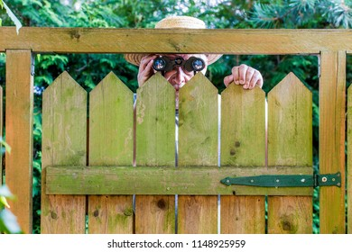a curious neighbor stands behind a fence and watches with binoculars