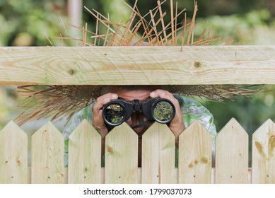 Curious neighbor stands behind a fence and watches