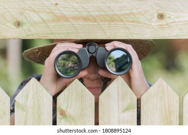 Curious neighbor stands behind a fence and watches with binoculars