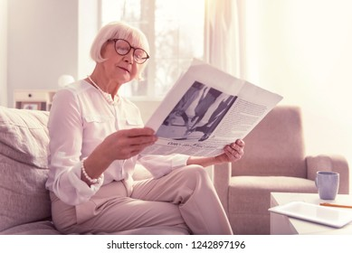 Curious old lady. Curious old lady attentively reading newspaper wearing big clear glasses and light clothes