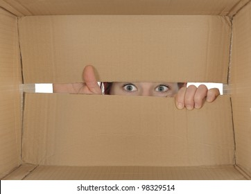 Curious person peering in a cardboard box