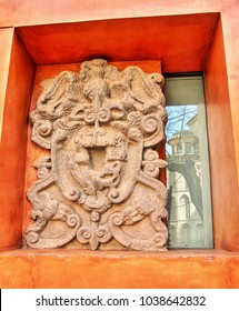 curious photograph of a relief next to a window pane, medieval shield in Toledo, Spain, old craft of stonemason