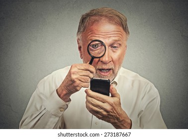 Curious. Portrait senior man investigator looking through magnifying glass at smart phone isolated grey wall background. Human face expression. Security safety or bad vision concept