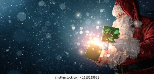 Curious Santa Claus opening magic gift box with copy space