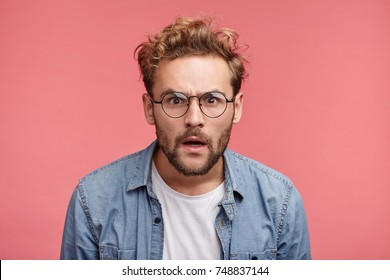 Curious scrupulous male model with trendy hairrdo and beard looks attentively at one point, sees something strange or suspicious. Angry man tries to overhear wife`s talk, looks annoyed, feels jealous