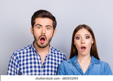 Curious shocked couple, standing in casual shirts, isolated on pure background with wonderment