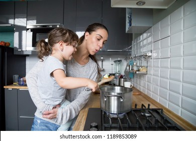 Curious small preschool cute girl tasting food in pan sitting on smiling single mother arms in kitchen, mom blowing on hot slice, child helping mother preparing food with cookware, family having fun