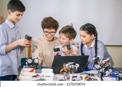 Curious smart caucasian pupils kids with female teacher enjoying science robotics lessons in technical school using laptop, study programming skill
