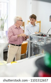 Curious student. Charming young man asking his senior supervisor questions about 3D printing while the man using a caliper