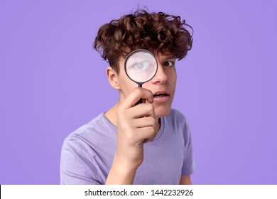 Curious teen boy with looking at camera through magnifying glass while searching for clues against violet background