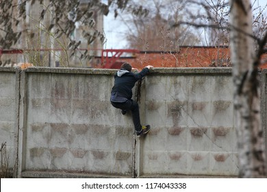 curious teenager moves through the concrete fence, the child climbs over the fence, cpling with his hands and pulling up, a guy hooligan enters the private area