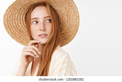 Curious thoughtful charming ginger girl with cute freckles in trendy summer straw hat turning right and gazing with interest and intrigued look touching chin while thinking and observing