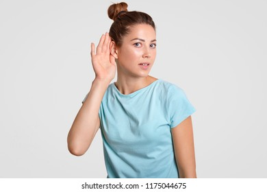 Curious woman puts hand near ear, tries to eavesdrop or overhear secret information, likes gossiping, dressed in casual blue t shirt, isolated over white background. Speak loudly to hear better you