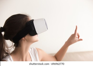 Curious woman in VR headset touching virtual world by finger, enjoying 3d tour, interacting with augmented reality digital interface, making purchases online, study in goggles, headshot, copy space