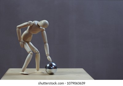 Curious wooden dummy bends to touch a steel ball. Gray background.