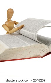 "Curious wooden person flipping through a book. Out of focus is a dictionary page with ""self"",  isolated white"