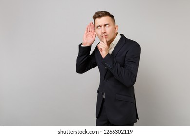 Curious young business man eavesdrop, hearing and saying hush be quiet with finger on lips, shhh gesture isolated on grey background. Achievement career wealth business concept. Mock up copy space