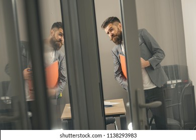 Curious young businessman looking through door in office.