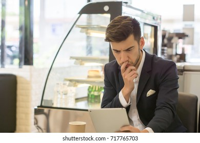 Curious young businessman watching something on his tablet.