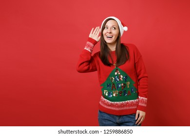 Curious young Santa girl in knitted sweater, Christmas hat eavesdrop, hearing gesture isolated on bright red wall background. Happy New Year 2019 celebration holiday party concept. Mock up copy space