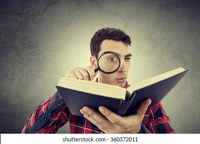 Curious young student man holding book with a magnifying glass.Perplexed Young man student holding magnifying glass and a book isolated over grey background.
