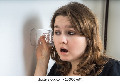 Curious young woman is listening and spying on neighbours behind wall.