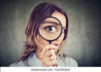 Curieuse jeune femme regardant à travers une loupe
