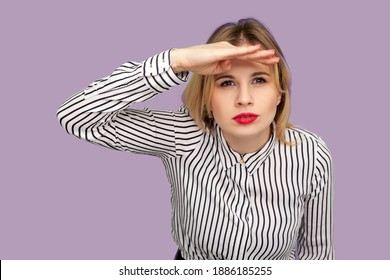 Curieuse jeune femme aux lèvres rouges en chemisier rayé gardant la paume sur la tête et regardant attentivement loin, regardant avec une attente de longue distance. tournage en studio isolé sur fond violet