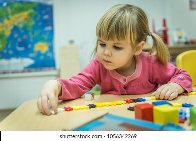 Curiously kid playin with puzzle toy in kindergarten
