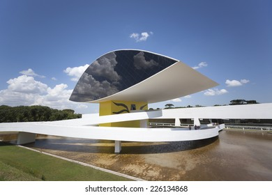 CURITIBA, BRAZIL Feb 4, 2014: Oscar Niemeyer Museum in Curitiba, Parana, Brazil with its eye-shaped monument and the reflection of passing clouds in the window front.