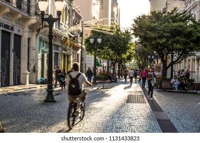 Curitiba, Brazil, January 03, 2018. Cyclist and pedestrians walking on Flower Street (Rua das Flores) in Downtown Curitiba, Parana State