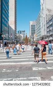 Curitiba - PR, Brazil - December 14, 2018: Downtown cross streets XV de Novembro and Marechal Floriano Peixoto. Rua das Flores. Touristic place. Commerce, people, pedestrians on crosswalk.