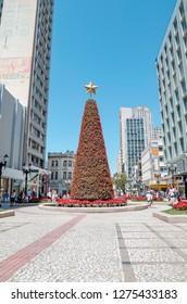 Curitiba - PR, Brazil - December 14, 2018: Big christmas tree on XV de Novembro street where it was the square's water fountain. Christmas tree decorated with flowers. Rua das Flores. Touristic place