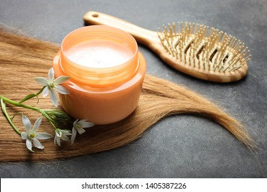 Curl female hair, balm or hair mask and bamboo comb on black background.