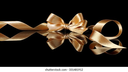 Curled golden ribbon with bow on a black background