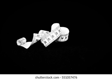 Curled measuring tape with centimeters in black and white isolated on a black background