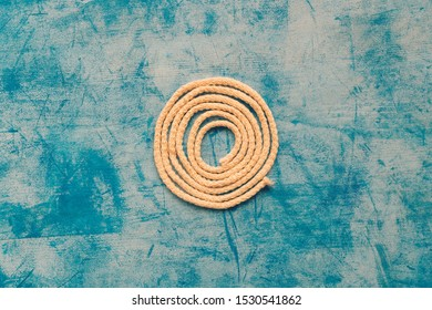 Curled rope on blue wooden background, rustic retro texture