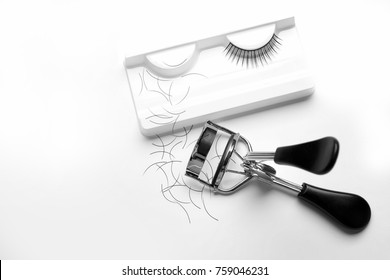 Curler and false eyelashes on white background