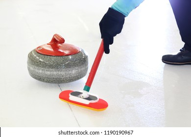 Curling games. The player is brushing the ice by directing the stone to the house.