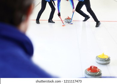 Curling games. The player is brushing the ice by directing the stone to the house