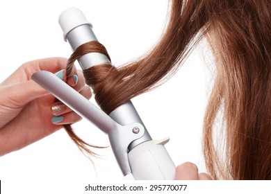 Curling iron and hair over white background