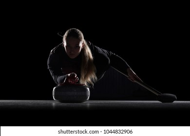 Curling player delivering a stone on a curling rink, sliding over the ice, isolated on the black background. Curling match curler athlete winter sport. Curling match curler athlete winter sports women