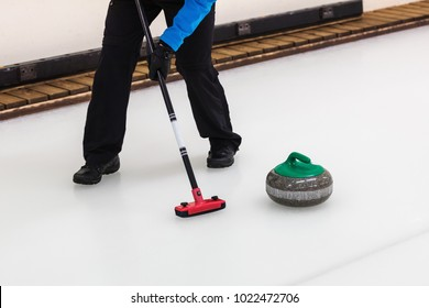 curling sport - player with broom sweeping the ice before stone