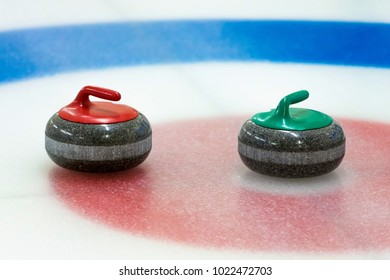 curling stones in the target on the ice