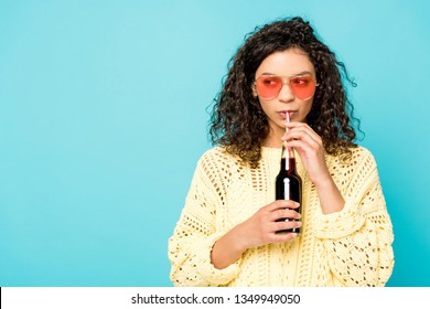 curly african american girl in sunglasses holding bottle with straw and drinking soda isolated on blue