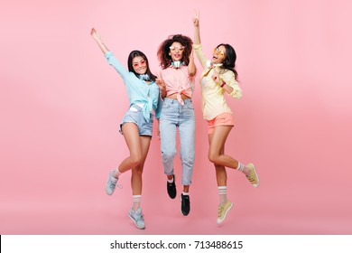 Curly african woman in jeans jumping while posing with international university friends. Tanned latin girl in yellow shirt dancing on pink background and having fun with other ladies.