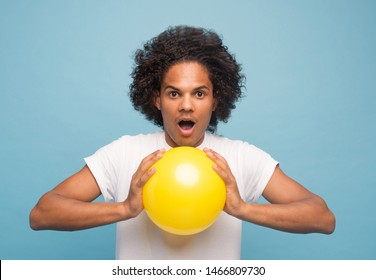curly afro american guy on a blue background in a white T-shirt with a ball. emotional portrait. Studio